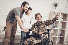 Disabled Woman Soldier Makes A Family Selfie. Disabled Woman In A Wheelchair Makes A Selfie With Family. Meeting After War. Son And Husband. Camouflage Uniform stock photography