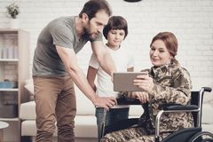Disabled Woman Soldier Watch A Tablet With Family. Disabled Woman In A Wheelchair Watch A Tablet With Family. Meeting After War. Son And Husband. Camouflage stock photography