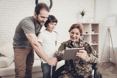Disabled Woman Soldier Watch A Tablet With Family. Disabled Woman In A Wheelchair Watch A Tablet With Family. Meeting After War. Son And Husband. Camouflage royalty free stock photos