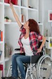 Disabled woman struggling reaching book on top shelf Royalty Free Stock Photos