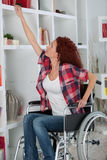Disabled woman struggling to reach book on shelf Royalty Free Stock Photos