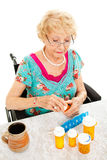 Disabled Woman Takes Medicine. Disabled senior woman in a wheelchair, counting out her medications for the week.  White background Stock Images