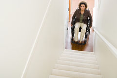 Disabled woman trapped at bottom of stairs Royalty Free Stock Photography