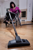 Disabled woman using vacuum cleaner Stock Image