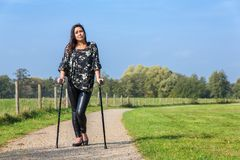 Disabled woman walks on crutches in nature. Disabled young woman walking on crutches in park Stock Photography