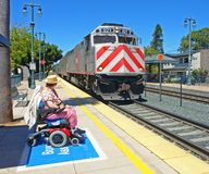 Disabled woman watching her train arrive. A disabled woman ready for boarding watches her Caltrain passenger train arrive Royalty Free Stock Photography