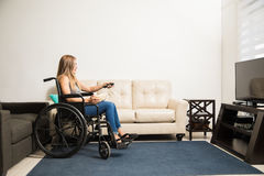 Disabled woman watching TV at home Royalty Free Stock Image