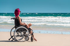 Disabled woman in the wheelchair. At the beach enjoying the view Stock Photography