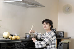 Disabled woman in wheelchair cooking dinner Royalty Free Stock Photos