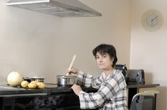 Disabled woman in wheelchair cooking dinner Royalty Free Stock Photography
