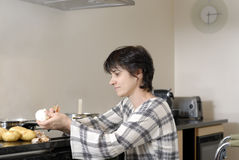 Disabled woman in wheelchair cooking dinner Stock Photography