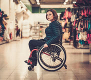 Disabled woman in a wheelchair in a department store Royalty Free Stock Photography
