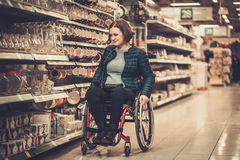 Disabled woman in a wheelchair in a department store Royalty Free Stock Photo