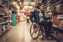 Disabled woman in a wheelchair in a department store Stock Photo