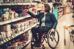 Disabled woman in a wheelchair in a department store Royalty Free Stock Photos