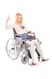 Disabled woman in a wheelchair giving thumb up Stock Image