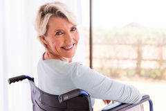 Disabled woman in wheelchair. Happy disabled woman in wheelchair looking back Stock Image