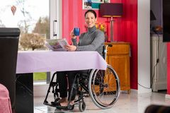 Disabled woman in wheelchair at home reading newspaper and drink royalty free stock images