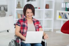 Disabled woman on wheelchair with laptop at home royalty free stock photography