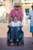 Disabled woman on a wheelchair. Love of an elderly couple. Royalty Free Stock Image