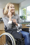 Disabled Woman In Wheelchair Making Call On Mobile Phone At Home Royalty Free Stock Image