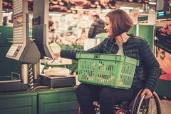 Disabled woman in a wheelchair near scales in a store Stock Photography