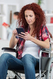 Disabled woman in wheelchair on phone Stock Images