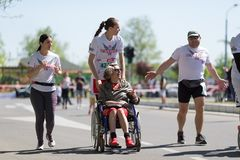 Disabled woman in wheelchair runs marathon race, helped by other runners royalty free stock photography