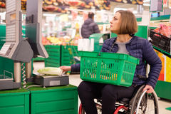 Disabled woman in a wheelchair in a store.  Royalty Free Stock Images
