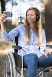 Disabled woman in wheelchair taking selfie Royalty Free Stock Photography