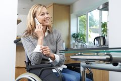 Disabled Woman In Wheelchair Talking On Mobile Phone At Home royalty free stock image