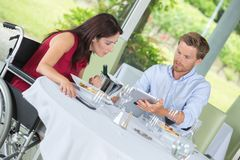 Disabled woman having lunch with husband in restaurant Stock Image