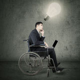 Disabled worker sitting under bright lamp Stock Images