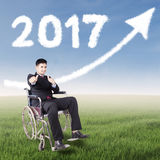 Disabled worker in under upward and 2017. Disabled worker showing thumbs up at field while sitting on the wheelchair with upward arrow and number 2017 on the sky Stock Photography