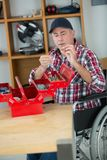 Disabled worker in wheelchair in carpenters workshop. Disabled worker in wheelchair in a carpenters workshop Royalty Free Stock Images