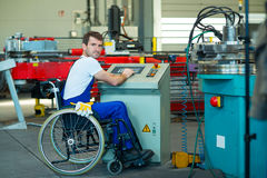 Disabled worker in wheelchair in factory and colleague Royalty Free Stock Images