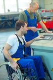 Disabled worker in wheelchair in factory and colleague Stock Image