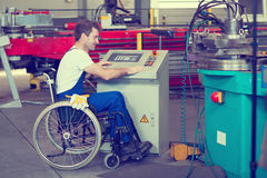 Disabled worker in wheelchair in factory. On the machine royalty free stock images