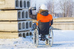 Disabled worker on wheelchair take photos on tablet in construction site. In winter day stock photography