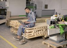 Disabled young man with artificial leg is working at the furniture factory. Disabled young man with an artificial leg is working at the furniture factory stock photo