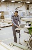 Disabled young man with artificial leg is working at the furniture factory. Disabled young man with an artificial leg is working at the furniture factory royalty free stock photography