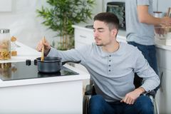 Disabled young man cooking meal in kitchen Stock Images