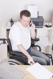 Disabled young man at the office. Young disabled man in wheelchair working in a home office having a phone call Stock Photos