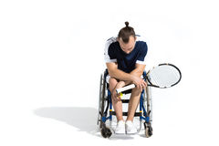Disabled young man sitting in wheelchair and holding tennis racquet Royalty Free Stock Photos