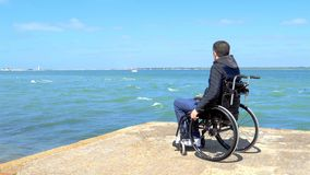 Disabled young man sitting in a wheelchair and looks at the sea stock video