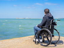 Disabled young man sitting in a wheelchair and looks at the sea royalty free stock images
