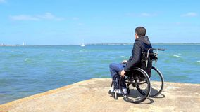 Disabled young man sitting in a wheelchair and looks at the sea slow motion stock video