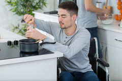 Disabled young man in wheelchair cooking in kitchen. Disabled young man in wheelchair is cooking in the kitchen Stock Photos