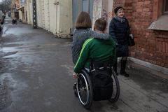 A disabled young man  in a wheelchair with  girl Royalty Free Stock Image