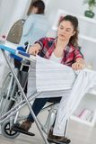 Disabled young pretty woman ironing in living room Royalty Free Stock Images
